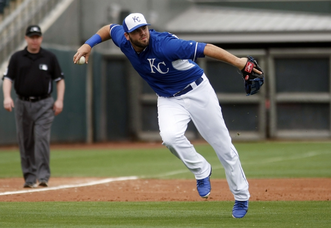 Mar 6, 2014; Surprise, AZ, USA; Kansas City Royals third baseman Mike Moustakas (8) tries to make the off balance throw for the out in the fourth inning against the Chicago White Sox at Surprise Stadium. Mandatory Credit: Rick Scuteri-USA TODAY Sports