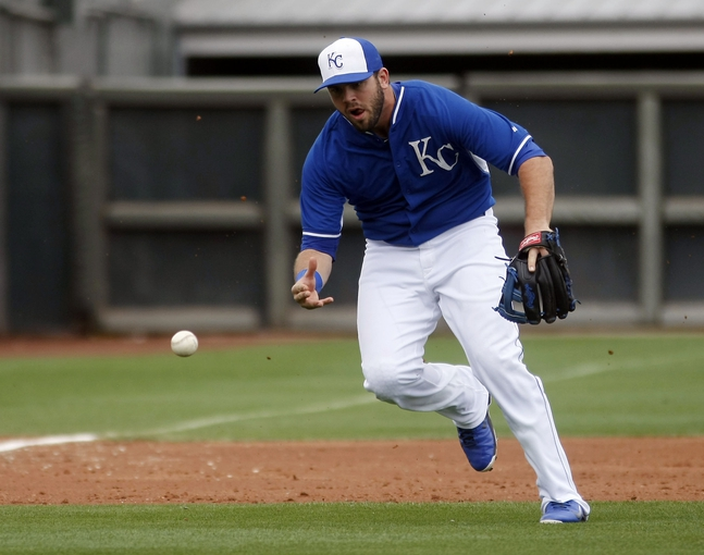 Mar 6, 2014; Surprise, AZ, USA; Kansas City Royals third baseman Mike Moustakas (8) tries to bare hand a ground ball in the fourth inning against the Chicago White Sox at Surprise Stadium. Mandatory Credit: Rick Scuteri-USA TODAY Sports