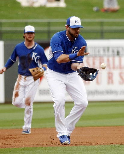Mar 6, 2014; Surprise, AZ, USA; Kansas City Royals third baseman Mike Moustakas (8) fields a ground ball against the Chicago White Sox in the third inning at Surprise Stadium. Mandatory Credit: Rick Scuteri-USA TODAY Sports
