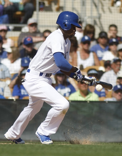 Mar 7, 2014; Phoenix, AZ, USA; Los Angeles Dodgers shortstop Dee Gordon (9) bunts against the Texas Rangers in the fifth inning at Camelback Ranch. Mandatory Credit: Rick Scuteri-USA TODAY Sports