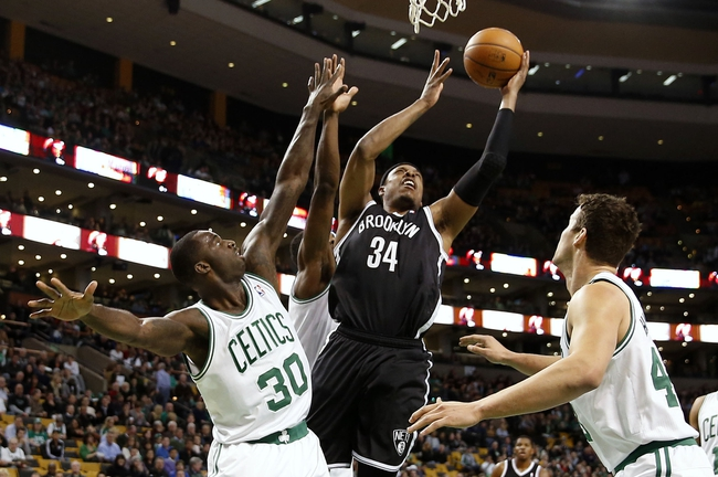 Mar 7, 2014; Boston, MA, USA; Brooklyn Nets small forward Paul Pierce (34) goes to the basket between Boston Celtics power forward Brandon Bass (30) and center Kris Humphries (43) during the first quarter at TD Garden. Mandatory Credit: Winslow Townson-USA TODAY Sports