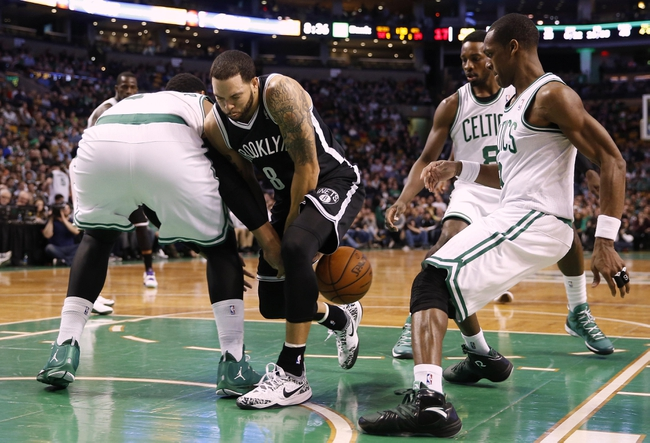 Mar 7, 2014; Boston, MA, USA; Brooklyn Nets point guard Deron Williams (8) has the ball knocked away from him by Boston Celtics center Jared Sullinger (7), left, as small forward Jeff Green (8) and point guard Rajon Rondo (9) look on during the second quarter at TD Garden. Mandatory Credit: Winslow Townson-USA TODAY Sports