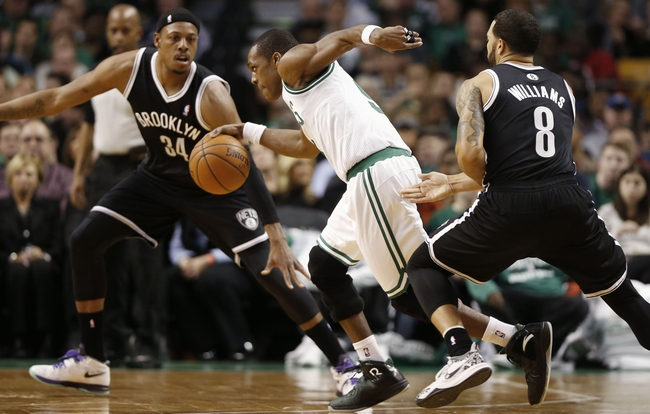 Mar 7, 2014; Boston, MA, USA; Boston Celtics point guard Rajon Rondo (9) cuts between Brooklyn Nets small forward Paul Pierce (34) and point guard Deron Williams (8) during the second quarter at TD Garden. Mandatory Credit: Winslow Townson-USA TODAY Sports