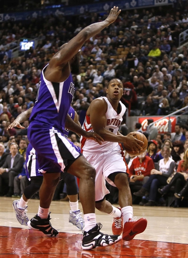 Mar 7, 2014; Toronto, Ontario, CAN; Toronto Raptors guard Kyle Lowry (7) drives to the net against Sacramento Kings forward Reggie Evans (30) at the Air Canada Centre. Toronto defeated Sacramento 99-87. Mandatory Credit: John E. Sokolowski-USA TODAY Sports