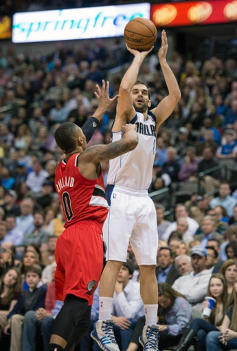 Mar 7, 2014; Dallas, TX, USA; Dallas Mavericks point guard Jose Calderon (8) shoots over Portland Trail Blazers point guard Damian Lillard (0) during the first half at the American Airlines Center. Mandatory Credit: Jerome Miron-USA TODAY Sports