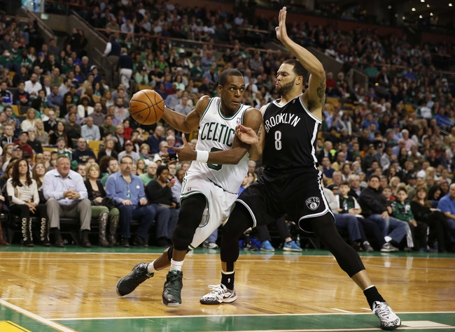 Mar 7, 2014; Boston, MA, USA; Boston Celtics point guard Rajon Rondo (9) drives past Brooklyn Nets point guard Deron Williams (8) during the second half of Boston's 91-84 win at TD Garden. Mandatory Credit: Winslow Townson-USA TODAY Sports