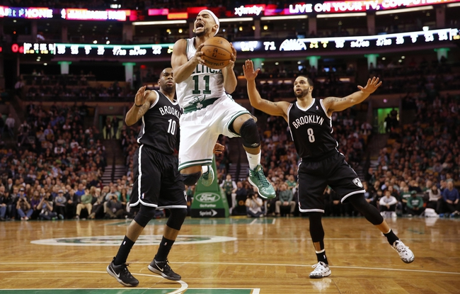 Mar 7, 2014; Boston, MA, USA; Boston Celtics point guard Jerryd Bayless (11) goes for a shot between Brooklyn Nets shooting guard Marcus Thornton (10) and point guard Deron Williams (8) during the second half of Boston's 91-84 win at TD Garden. Mandatory Credit: Winslow Townson-USA TODAY Sports
