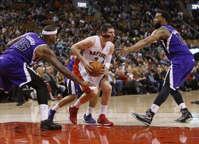 Mar 7, 2014; Toronto, Ontario, CAN; Toronto Raptors guard Nando De Colo (3) tries to get between Sacramento Kings center DeMarcus Cousins (15) and  forward Derrick Williams (13) during the second half at the Air Canada Centre. Toronto defeated Sacramento 99-87. Mandatory Credit: John E. Sokolowski-USA TODAY Sports