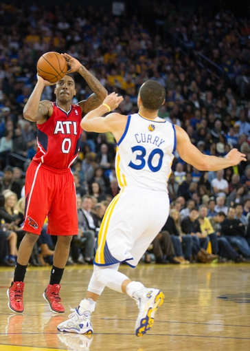 Mar 7, 2014; Oakland, CA, USA; Atlanta Hawks point guard Jeff Teague (0) scores a three point basket against Golden State Warriors point guard Stephen Curry (30) during the second quarter at Oracle Arena. Mandatory Credit: Kelley L Cox-USA TODAY Sports