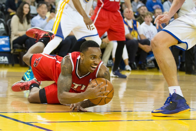 Mar 7, 2014; Oakland, CA, USA; Atlanta Hawks point guard Jeff Teague (0) tries to maintain possession as he slips against Golden State Warriors power forward David Lee (10) during the second quarter at Oracle Arena. Mandatory Credit: Kelley L Cox-USA TODAY Sports