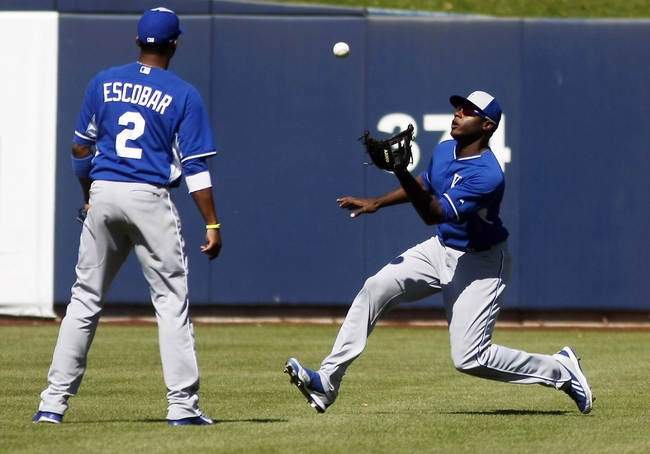 Mar 8, 2014; Phoenix, AZ, USA; Kansas City Royals center fielder Lorenzo Cain (6) makes the catch in front of shortstop Alcides Escobar (2) in the fourth inning against the Milwaukee Brewers at Maryvale Baseball Park. Mandatory Credit: Rick Scuteri-USA TODAY Sports