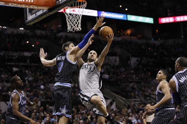 Mar 8, 2014; San Antonio, TX, USA; San Antonio Spurs guard Manu Ginobili (20) shoots while being defended by Orlando Magic center Nikola Vucevic (9) during the first half at AT&T Center. Mandatory Credit: Soobum Im-USA TODAY Sports
