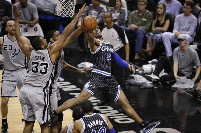 Mar 8, 2014; San Antonio, TX, USA; Orlando Magic guard Arron Afflalo (4) shoot the ball as San Antonio Spurs forward Boris Diaw (33) and Tim Duncan (behind) defend during the first half at AT&T Center. Mandatory Credit: Soobum Im-USA TODAY Sports