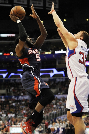 Mar 8, 2014; Los Angeles, CA, USA; Atlanta Hawks forward DeMarre Carroll (5) attempts a shot while defended by Los Angeles Clippers forward Blake Griffin (32) during the first quarter at Staples Center. Mandatory Credit: Kelvin Kuo-USA TODAY Sports