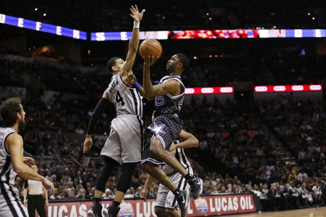 Mar 8, 2014; San Antonio, TX, USA; Orlando Magic guard E'Twaun Moore (55) shoots the ball as San Antonio Spurs guard Danny Green (4) defends during the second half at AT&T Center. The Spurs won 121-112. Mandatory Credit: Soobum Im-USA TODAY Sports