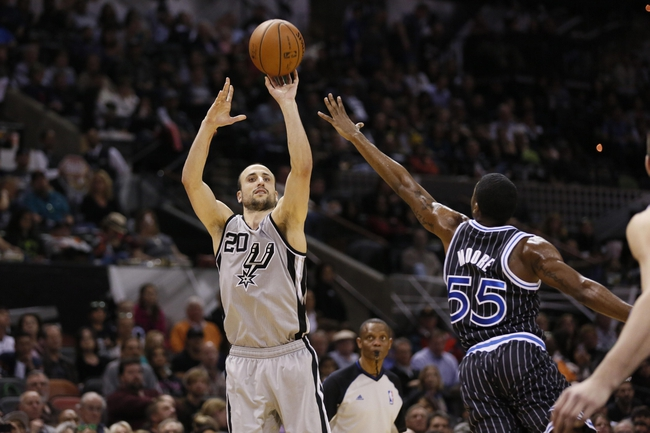 Mar 8, 2014; San Antonio, TX, USA; San Antonio Spurs guard Manu Ginobili (20) shoots the ball over Orlando Magic guard E'Twaun Moore (55) during the second half at AT&T Center. The Spurs won 121-112. Mandatory Credit: Soobum Im-USA TODAY Sports