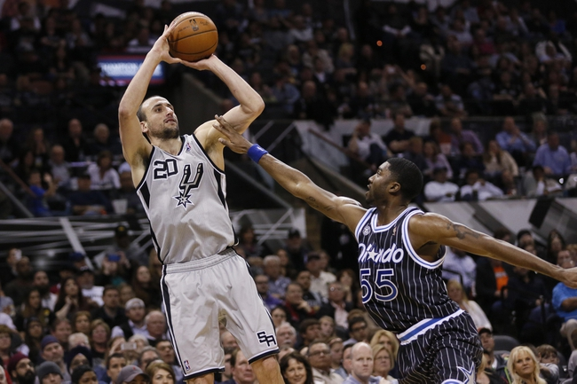 Mar 8, 2014; San Antonio, TX, USA; San Antonio Spurs guard Manu Ginobili (20) shots the ball over Orlando Magic guard E'Twaun Moore (55) during the second half at AT&T Center. The Spurs won 121-112. Mandatory Credit: Soobum Im-USA TODAY Sports