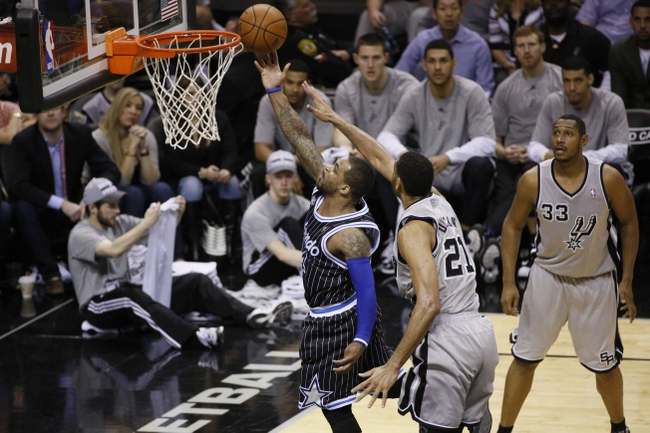 Mar 8, 2014; San Antonio, TX, USA; Orlando Magic guard Arron Afflalo (4) shoots the ball past San Antonio Spurs forward Tim Duncan (21) during the second half at AT&T Center. The Spurs won 121-112. Mandatory Credit: Soobum Im-USA TODAY Sports