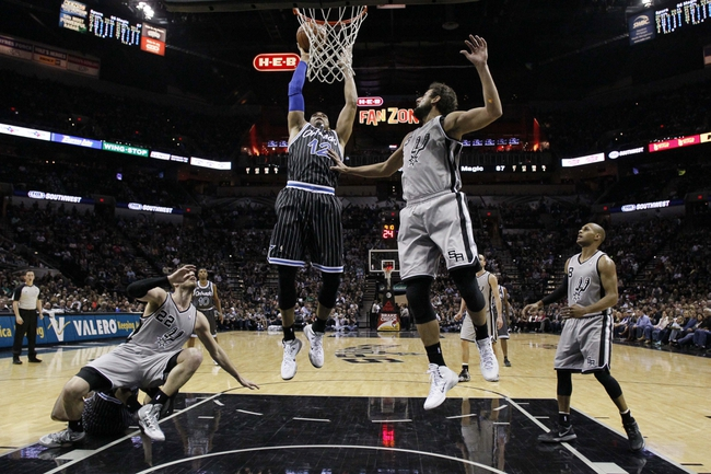 Mar 8, 2014; San Antonio, TX, USA; Orlando Magic forward Tobias Harris (12) shoots the ball past San Antonio Spurs forward Marco Belinelli (3) during the second half at AT&T Center. The Spurs won 121-112. Mandatory Credit: Soobum Im-USA TODAY Sports
