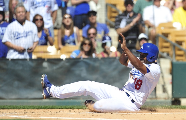 Mar 9, 2014; Glendale, AZ, USA; Los Angeles Dodgers left fielder Chone Figgins (18) slides home to score a run in the first inning against the San Francisco Giants at Camelback Ranch. Mandatory Credit: Gary A. Vasquez-USA TODAY Sports