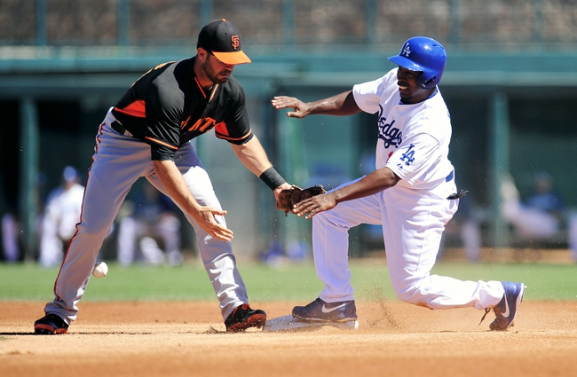 Mar 9, 2014; Glendale, AZ, USA; Los Angeles Dodgers left fielder Chone Figgins (18) steals second against the tag of San Francisco Giants shortstop Brandon Hicks (14) in the first inning at Camelback Ranch. Mandatory Credit: Gary A. Vasquez-USA TODAY Sports