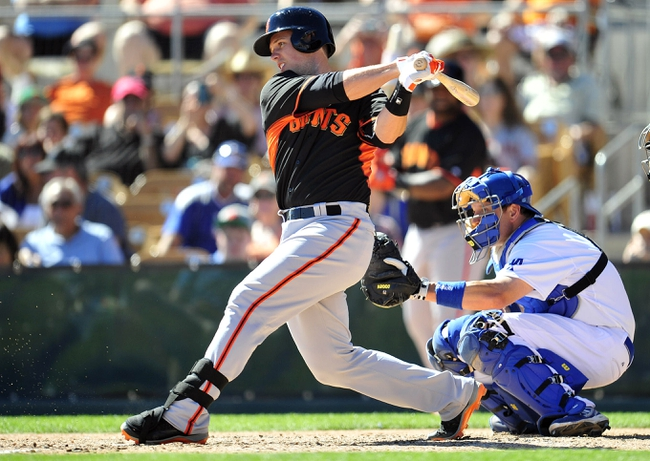 Mar 9, 2014; Glendale, AZ, USA; San Francisco Giants catcher Buster Posey (28) hits a single in the fourth inning against the Los Angeles Dodgers at Camelback Ranch. Mandatory Credit: Gary A. Vasquez-USA TODAY Sports