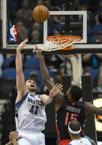Mar 9, 2014; Minneapolis, MN, USA; Minnesota Timberwolves power forward Kevin Love (42) goes up for a layup past Toronto Raptors power forward Amir Johnson (15) in the first half at Target Center. Mandatory Credit: Jesse Johnson-USA TODAY Sports