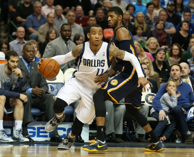 Mar 9, 2014; Dallas, TX, USA; Dallas Mavericks guard Monta Ellis (11) drives against Indiana Pacers guard froward Paul George (24) in the fourth quarter at American Airlines Center. The Mavs beat the Pacers 105-94. Mandatory Credit: Matthew Emmons-USA TODAY Sports