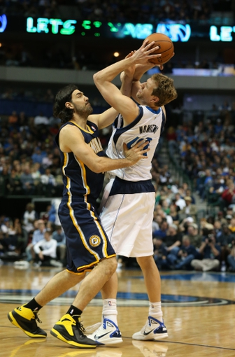 Mar 9, 2014; Dallas, TX, USA; Dallas Mavericks forward Dirk Nowitzki (41) looks to pass in the second half s he gets fouled by Indiana Pacers forward Luis Scola (4) at American Airlines Center. The Mavs beat the Pacers 105-94. Mandatory Credit: Matthew Emmons-USA TODAY Sports