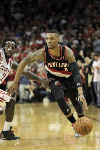 Mar 9, 2014; Houston, TX, USA; Portland Trail Blazers point guard Damian Lillard (0) drives to the basket past Houston Rockets point guard Patrick Beverley (2) during the fourth quarter at Toyota Center. Mandatory Credit: Andrew Richardson-USA TODAY Sports