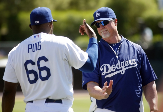 Mar 10, 2014; Phoenix, AZ, USA; Los Angeles Dodgers right fielder Yasiel Puig (66) talks to hitting coach Mark McGwire (25) before a game against the Oakland Athletics at Camelback Ranch. Mandatory Credit: Rick Scuteri-USA TODAY Sports