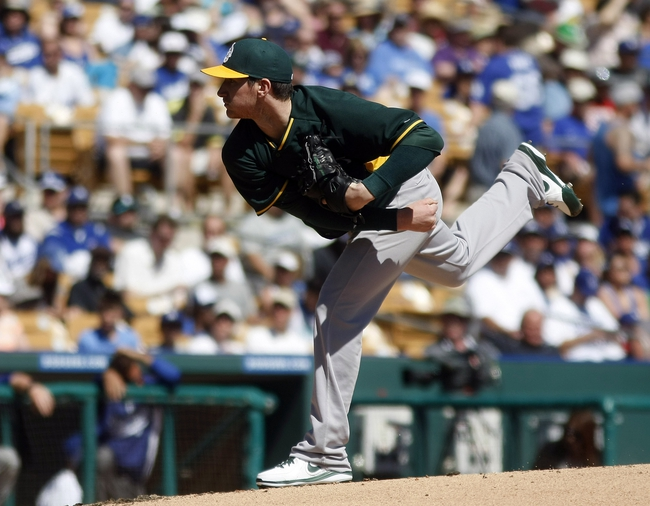 Mar 10, 2014; Phoenix, AZ, USA; Oakland Athletics starting pitcher Jarrod Parker (11) throws in the first inning against the Los Angeles Dodgers at Camelback Ranch. Mandatory Credit: Rick Scuteri-USA TODAY Sports