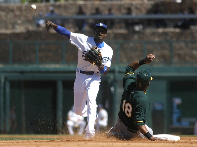 Mar 10, 2014; Phoenix, AZ, USA; Los Angeles Dodgers shortstop Dee Gordon (9) turns the double play while avoiding Oakland Athletics second baseman Alberto Callaspo (18) in the second inning at Camelback Ranch. Mandatory Credit: Rick Scuteri-USA TODAY Sports