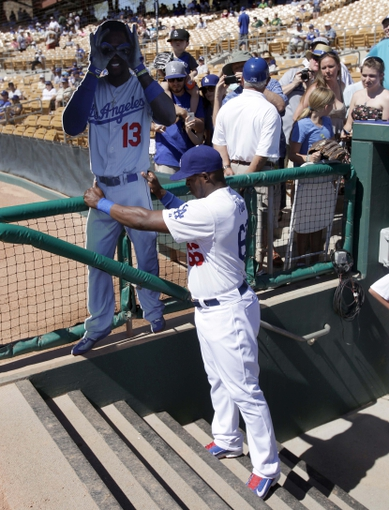 Mar 10, 2014; Phoenix, AZ, USA; Los Angeles Dodgers right fielder Yasiel Puig (66) sets up a life size cut out of shortstop Hanley Ramirez (13) before a game against the Oakland Athletics at Camelback Ranch. Mandatory Credit: Rick Scuteri-USA TODAY Sports
