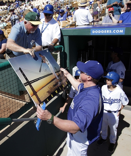 Mar 10, 2014; Phoenix, AZ, USA; Los Angeles Dodgers hitting coach Mark McGwire autographs a poster for a fan before a game against the Oakland Athletics at Camelback Ranch. Mandatory Credit: Rick Scuteri-USA TODAY Sports