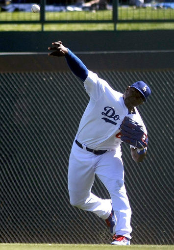 Mar 10, 2014; Phoenix, AZ, USA; Los Angeles Dodgers right fielder Yasiel Puig (66) tries to throw the runner out at first base in the fourth inning against the Oakland Athletics at Camelback Ranch. Mandatory Credit: Rick Scuteri-USA TODAY Sports