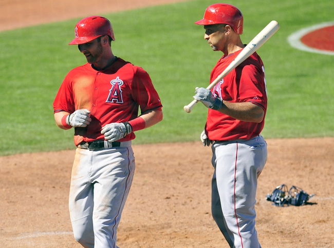 March 10, 2014; Goodyear, AZ, USA; Los Angeles Angels third baseman Andrew Romine (7) reacts with left fielder Raul Ibanez (28) after scoring a run in the fourth inning against the Cleveland Indians at Goodyear Ballpark. Mandatory Credit: -USA TODAY Sports