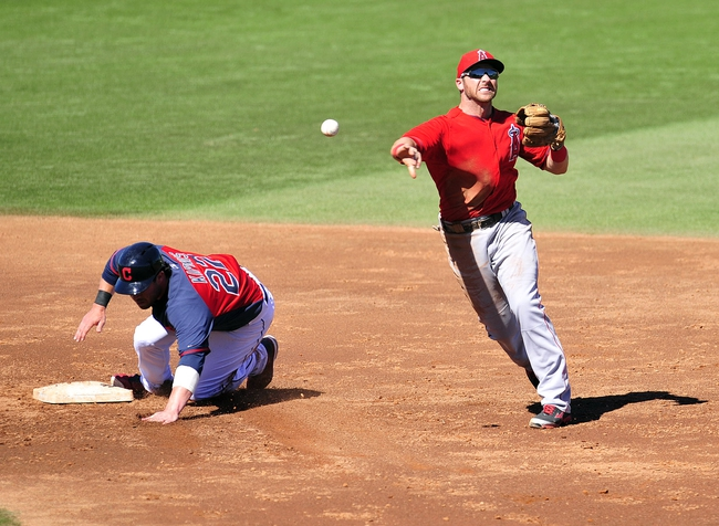 March 10, 2014; Goodyear, AZ, USA; Los Angeles Angels third baseman Andrew Romine (7) throws to first to complete an out as Cleveland Indians second baseman Jason Kipnis (22) is out at second in the third inning  at Goodyear Ballpark. Mandatory Credit: -USA TODAY Sports