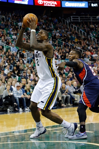 Mar 10, 2014; Salt Lake City, UT, USA; Utah Jazz power forward Marvin Williams (2) is tripped by Atlanta Hawks point guard Shelvin Mack (8) while shooting the ball during the third quarter at EnergySolutions Arena. The Atlanta Hawks won the game 112-110. Mandatory Credit: Chris Nicoll-USA TODAY Sports