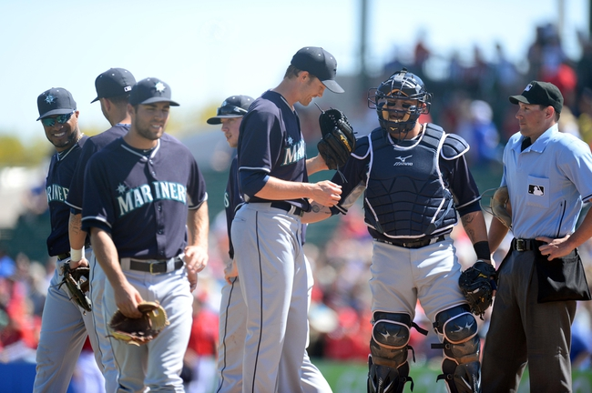 Mar 11, 2014; Tempe, AZ, USA; Seattle Mariners starting pitcher Scott Baker (58) meets with teammates in the first inning after hitting three Los Angeles Angels batters at Tempe Diablo Stadium. Mandatory Credit: Joe Camporeale-USA TODAY Sports
