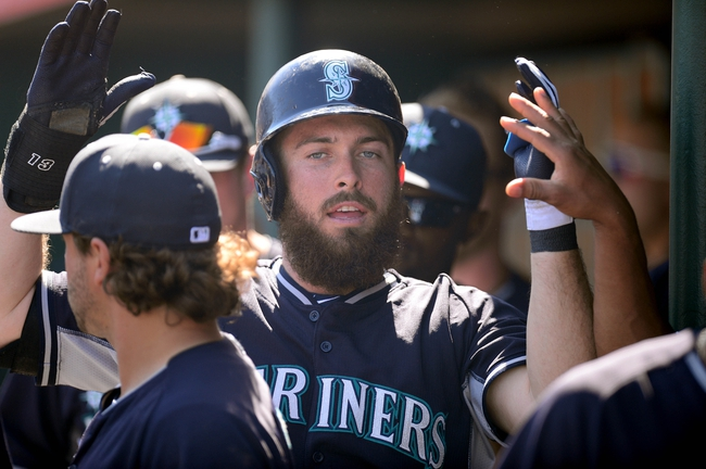 Mar 11, 2014; Tempe, AZ, USA; Seattle Mariners center fielder Dustin Ackley (13) is congratulated by teammates after scoring a run against the Los Angeles Angels at Tempe Diablo Stadium. Mandatory Credit: Joe Camporeale-USA TODAY Sports