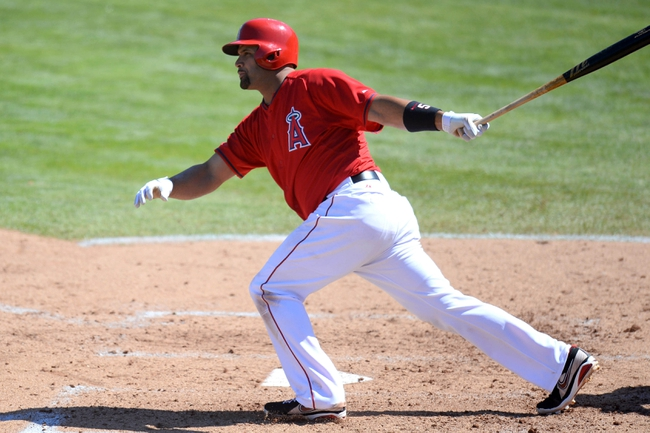 Mar 11, 2014; Tempe, AZ, USA; Los Angeles Angels first baseman Albert Pujols (5) hits an RBI double against the Seattle Mariners at Tempe Diablo Stadium. Mandatory Credit: Joe Camporeale-USA TODAY Sports