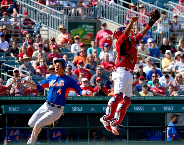 Mar 11, 2014; Jupiter, FL, USA; New York Mets third baseman Wilmer Flores (4) scores a run as St. Louis Cardinals catcher Audry Perez (63) leaps for a high throw at Roger Dean Stadium. The Mets defeated the Cardinals 9-8. Mandatory Credit: Scott Rovak-USA TODAY Sports