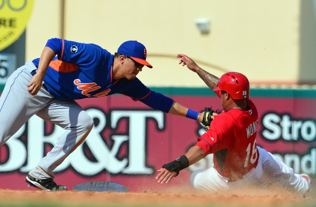 Mar 11, 2014; Jupiter, FL, USA; St. Louis Cardinals second baseman Kolten Wong (16) is tagged out by New York Mets third baseman Wilmer Flores (4) at Roger Dean Stadium. The Mets defeated the Cardinals 9-8. Mandatory Credit: Scott Rovak-USA TODAY Sports