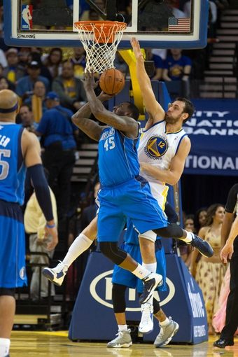 Mar 11, 2014; Oakland, CA, USA; Golden State Warriors center Andrew Bogut (12) fouls Dallas Mavericks center DeJuan Blair (45) during the third quarter at Oracle Arena. The Golden State Warriors defeated the Dallas Mavericks 108-85. Mandatory Credit: Kelley L Cox-USA TODAY Sports