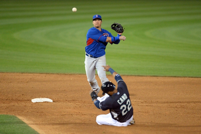 Mar 12, 2014; Peoria, AZ, USA; Seattle Mariners second baseman Robinson Cano (22) is unable to break up a double play by Chicago Cubs shortstop Javier Baez (70) at Peoria Sports Complex. Mandatory Credit: Joe Camporeale-USA TODAY Sports