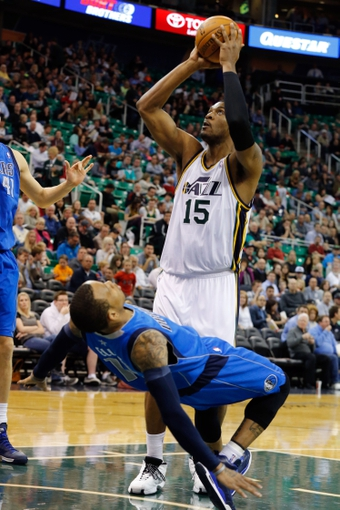 Mar 12, 2014; Salt Lake City, UT, USA; Utah Jazz center Derrick Favors (15) runs into Dallas Mavericks guard Monta Ellis (11) while shooting the ball during the third quarter at EnergySolutions Arena. Mandatory Credit: Chris Nicoll-USA TODAY Sports