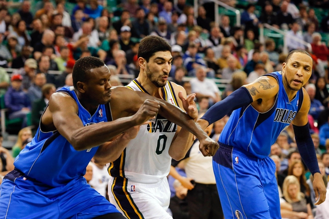 Mar 12, 2014; Salt Lake City, UT, USA; Utah Jazz center Enes Kanter (0) is elbowed in the throat by Dallas Mavericks center Samuel Dalembert (1) after a foul shot is taken during the fourth quarter at EnergySolutions Arena. Mandatory Credit: Chris Nicoll-USA TODAY Sports