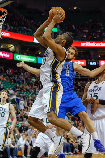 Mar 12, 2014; Salt Lake City, UT, USA; Utah Jazz guard Alec Burks (10) is fouled by Dallas Mavericks guard Jose Calderon (8) while shooting the ball during the fourth quarter at EnergySolutions Arena. Mandatory Credit: Chris Nicoll-USA TODAY Sports