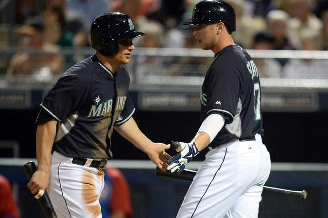 Mar 12, 2014; Peoria, AZ, USA; Seattle Mariners third baseman Kyle Seager (15) slaps hands with first baseman Justin Smoak (17) after scoring a run against the Chicago Cubs at Peoria Sports Complex. Mandatory Credit: Joe Camporeale-USA TODAY Sports